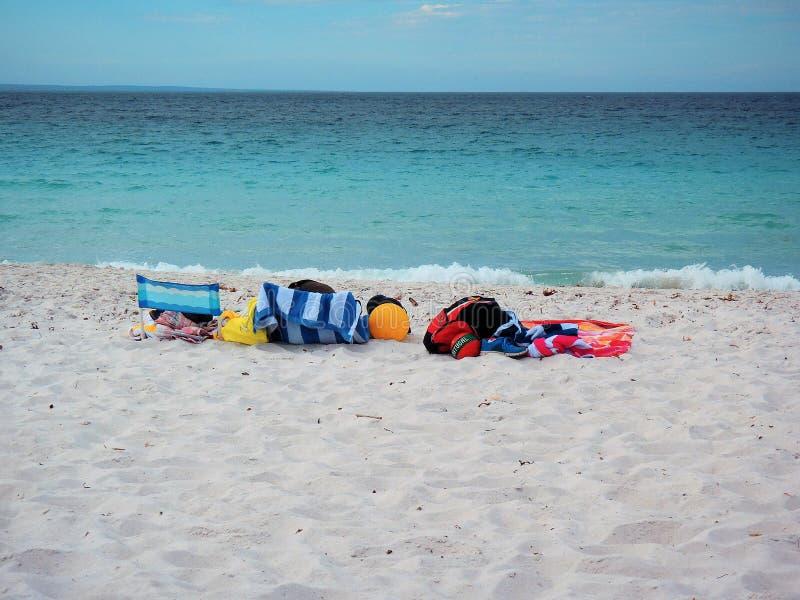 Asciugamani, sedie e palle di spiaggia variopinti sulla spiaggia di sabbia bianca immagine stock libera da diritti