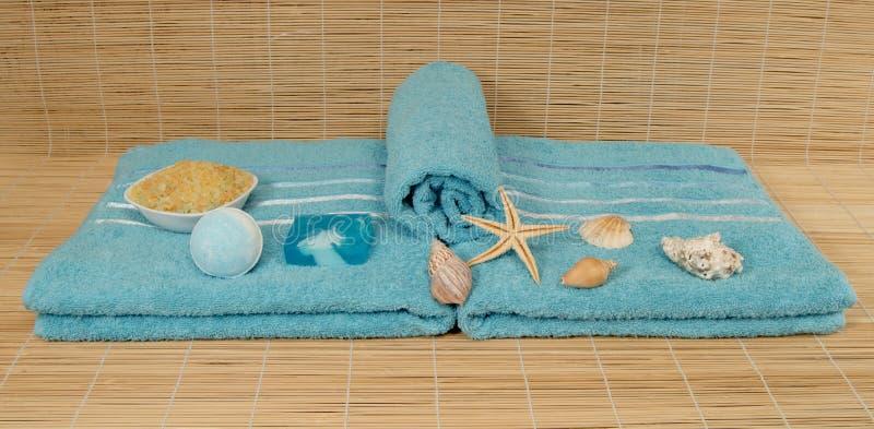 Asciugamano blu con le coperture, sale marino sulla stuoia di bambù immagini stock libere da diritti