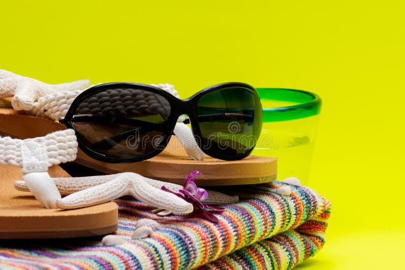 Asciugamano di spiaggia a strisce variopinto, Flip Flops causale delle donne, Rim Glass blu con acqua e gli occhiali da sole neri immagini stock