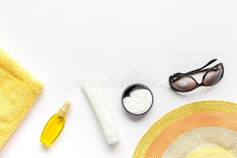 Asciugamano, lozione del sole, vetri sullo spazio bianco di vista superiore del fondo per testo immagine stock
