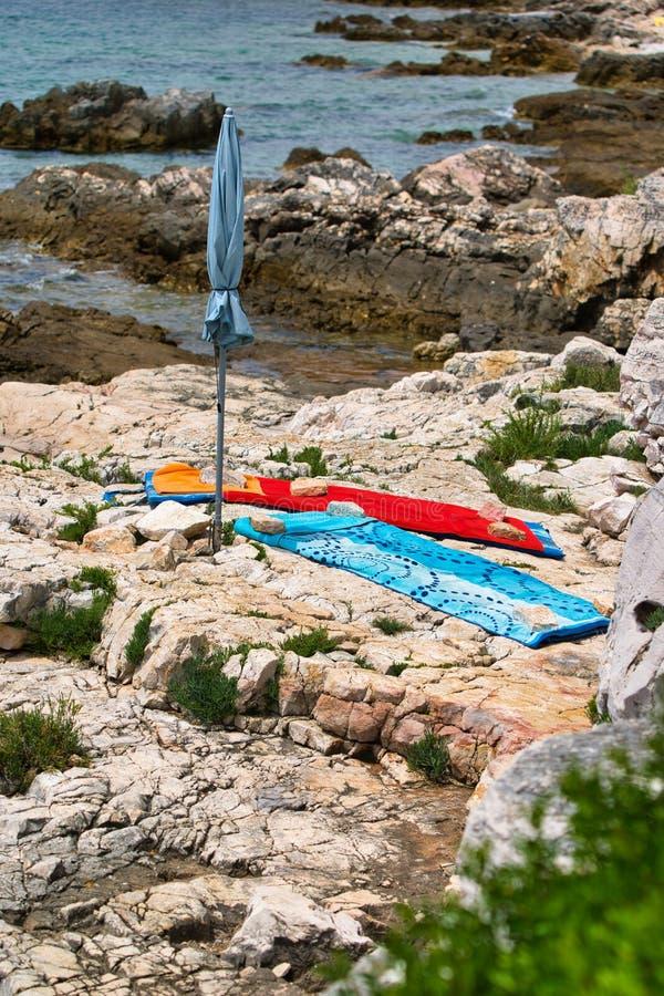 Asciugamano rosso e blu sulla spiaggia rocciosa immagini stock
