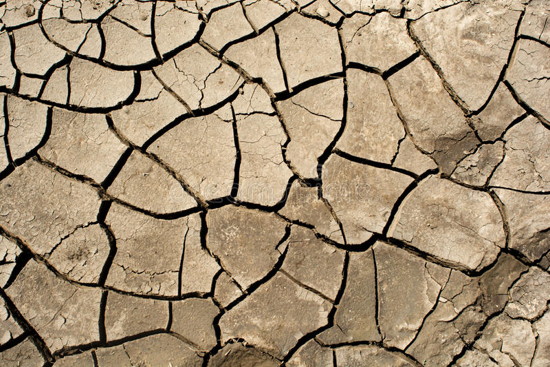 Asciughi il fondo incrinato della terra, struttura del deserto dell'argilla immagini stock