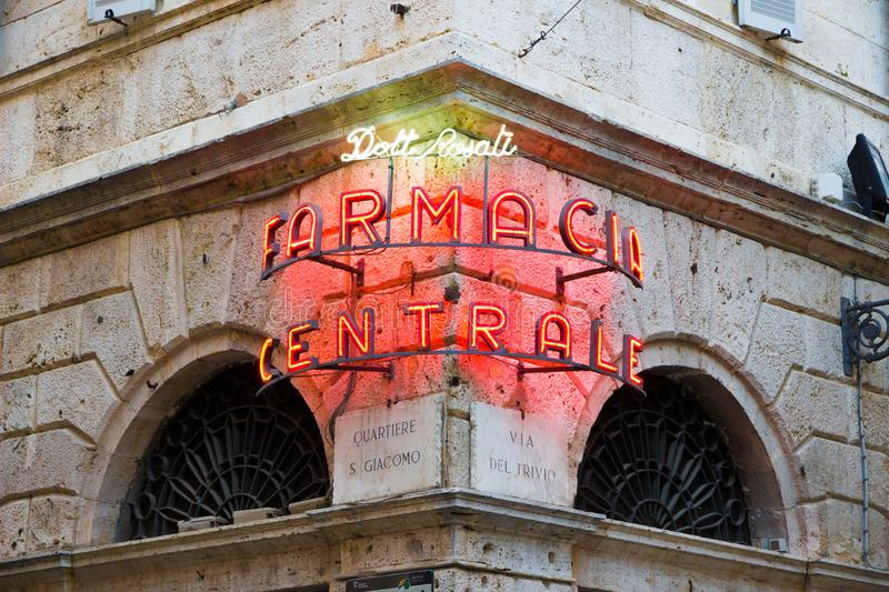Pharmacy neon sign in the old town of Ascoli Piceno, Italy stock photography