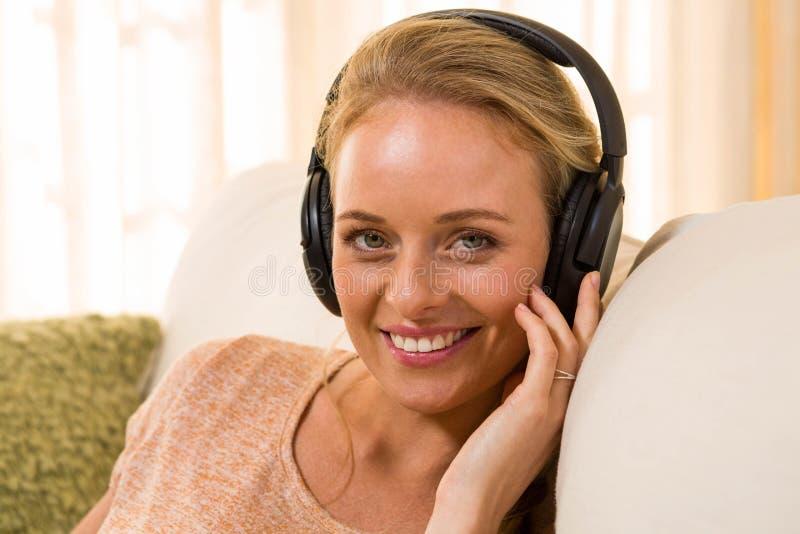 Ascoltare biondo grazioso la musica con le cuffie fotografia stock