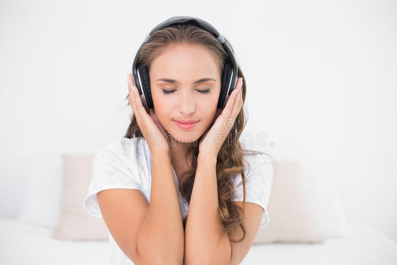 Ascoltare castana attraente contento la musica con gli occhi chiusi fotografie stock