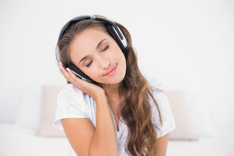Ascoltare castana sorridente pacifico la musica con gli occhi chiusi fotografia stock libera da diritti