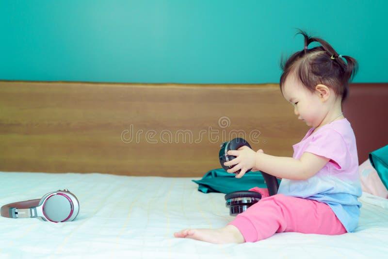 Ascoltare di seduta della bambina una grande cuffia avricolare nel letto nella camera da letto felicemente fotografia stock