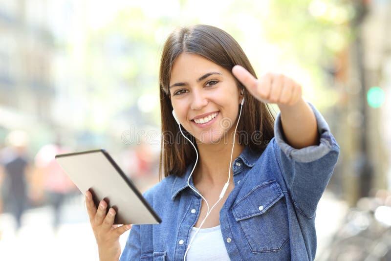Ascoltare teenager la musica con i pollici su fotografia stock libera da diritti