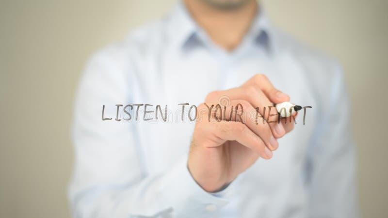 Ascolti il vostro cuore, scrittura dell'uomo sullo schermo trasparente fotografia stock libera da diritti