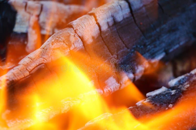 Ascuas que brillan intensamente en el color rojo caliente, fondo abstracto. Las ascuas calientes del fuego de registro de madera a imagen de archivo