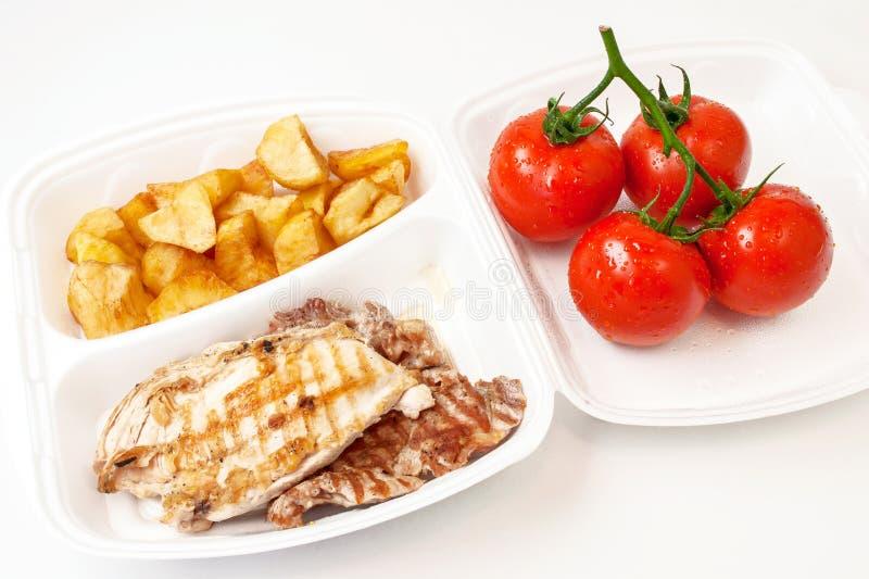 Ase la carne, las patatas y los tomates frescos en una cazuela fotografía de archivo libre de regalías