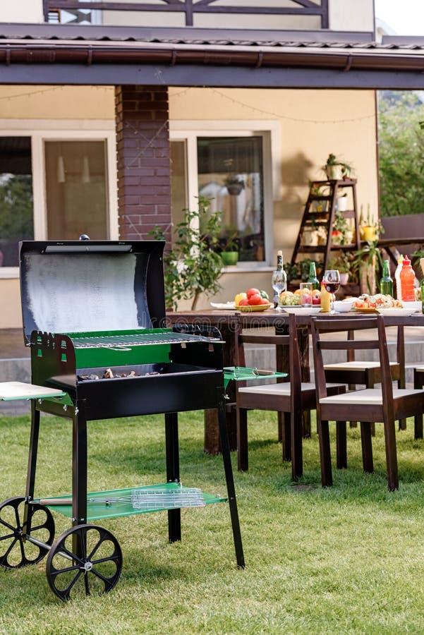 Ase a la parrilla con los carbones que se colocan en césped verde y la tabla servida con los platos y las bebidas detrás fotografía de archivo