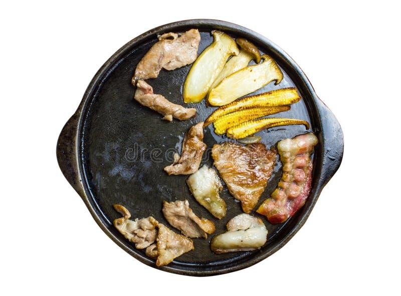 Ase a la parrilla el cerdo, carne de vaca, seta del origen, maíz joven, tocino en la placa de metal negra caliente fotografía de archivo
