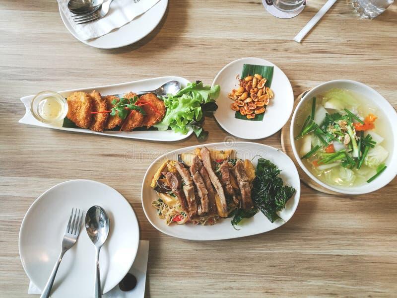 Ase a la parrilla el pato y los tallarines fritos servidos con la fritada curruscante de la albahaca pancack del camarón y comida foto de archivo