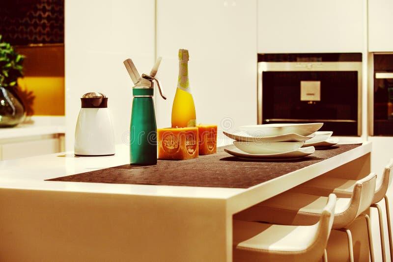 Ase på en induktion Detalj av en tabell med häverten, kaffemaskin, flaska av vin 2 royaltyfri foto