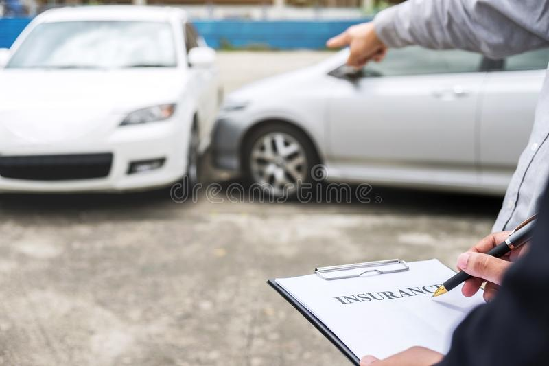 Asekuracyjny agent egzamininuje Uszkadzającego samochód i segregowania żądania Raportową formę zdjęcia stock