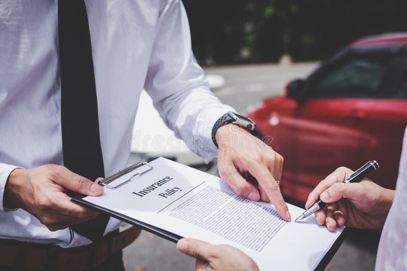 Asekuracyjny agent egzamininuje Uszkadzającego samochodu i klienta segregowania signatur obrazy royalty free