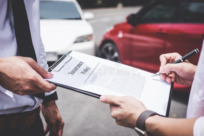 Asekuracyjny agent egzamininuje Uszkadzającego samochodu i klienta segregowania signatur fotografia stock