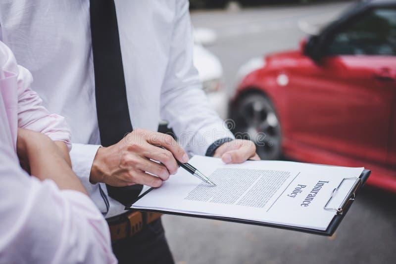 Asekuracyjny agent egzamininuje Uszkadzającego samochodu i klienta segregowania signatur fotografia royalty free