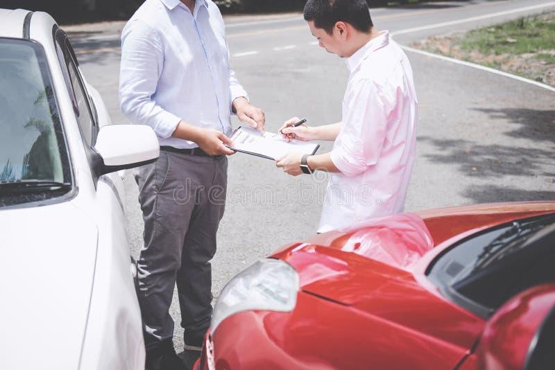 Asekuracyjny agent egzamininuje Uszkadzającego samochodu i klienta segregowania signatur zdjęcie royalty free