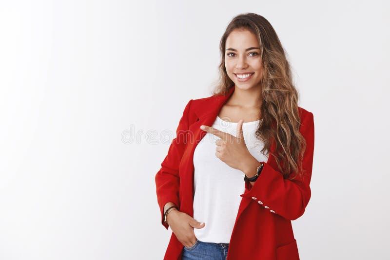 Asertoryczny atrakcyjny żeński przedsiębiorca stoi ufnej pozy ręki kieszeniowego wskazuje palec wskazującego na boku pokazuje kop obrazy stock