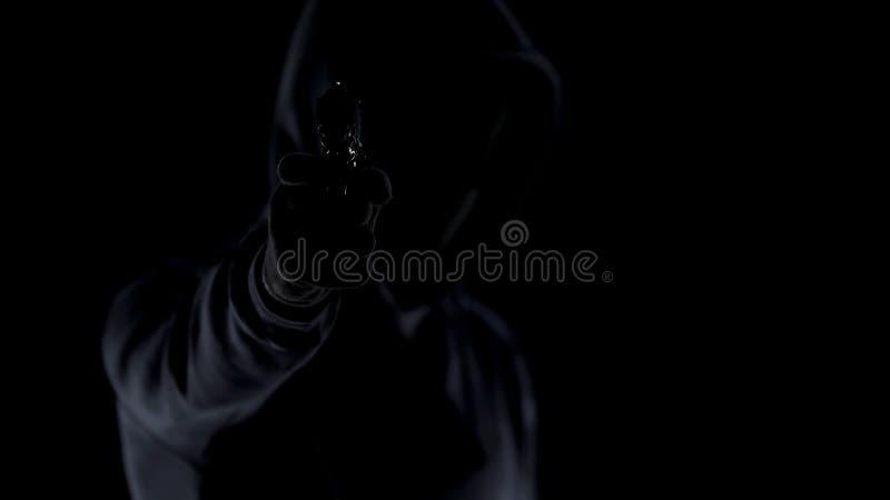 Asesino cruel en la ropa negra que apunta el arma a la cámara, asesinato del contrato, tiroteo fotografía de archivo libre de regalías