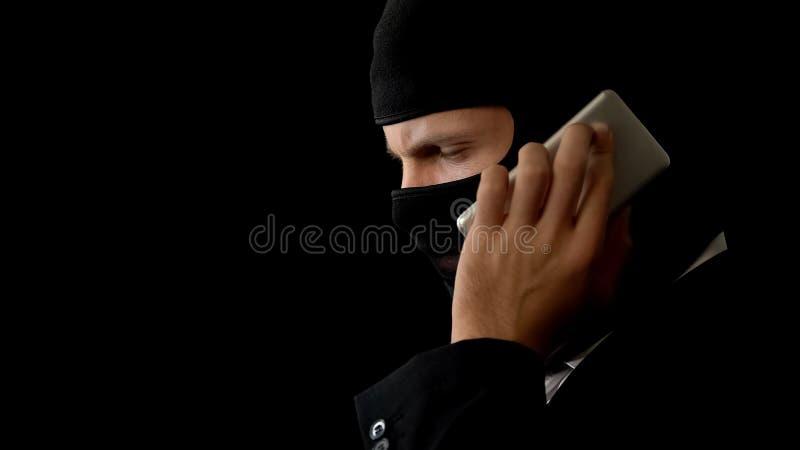 Asesino en pasamontañas que habla en el teléfono, crimen de planificación con los socios, corrupción imagen de archivo