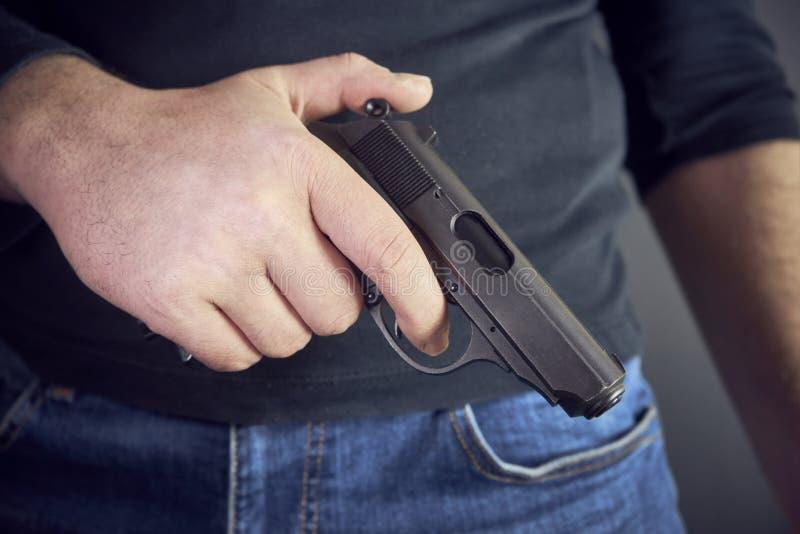 Asesino que lleva a cabo un lado del arma él, tiro cosechado del hombre que sostiene el arma disponible imagen de archivo libre de regalías