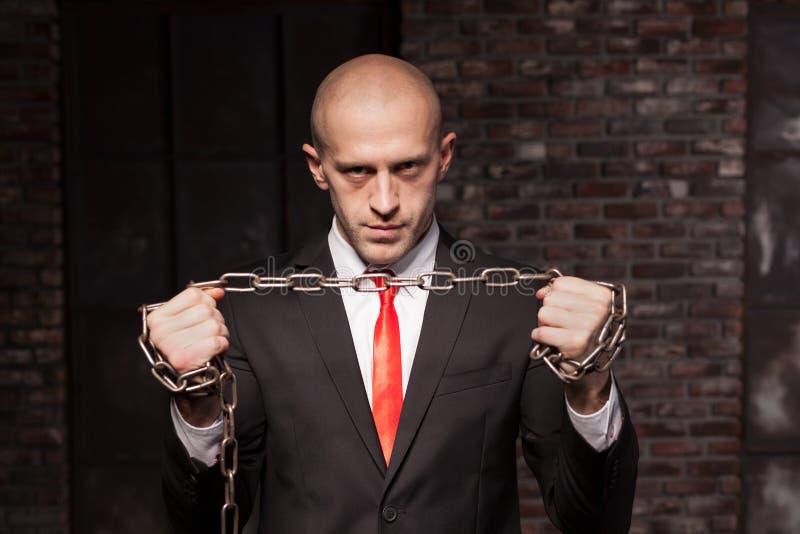 Asesino silencioso con la cadena del hierro en manos imagen de archivo