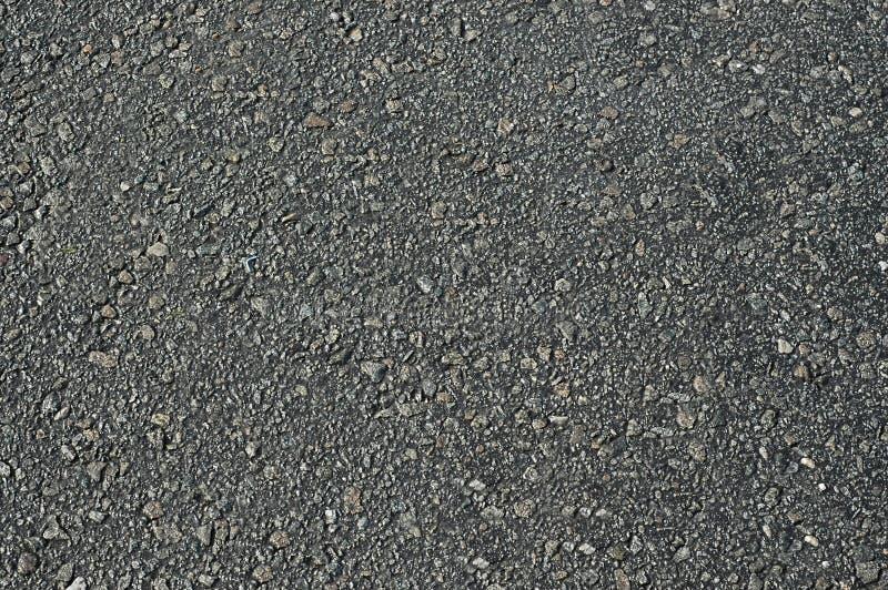 Asfalte a estrada com escuro desigual - superf?cie textured cinzenta Fundo foto de stock
