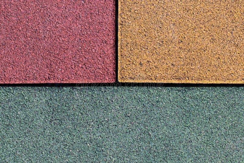 Asfalte los sectores amarillos, rojos y del verde del fondo de la textura foto de archivo