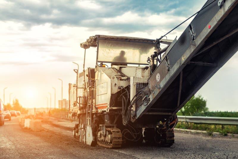 Asfaltera att mala och den malande maskinen på vägreparations- och konstruktionsplatsen Huvudvägförnyande med tungt maskineri royaltyfria bilder