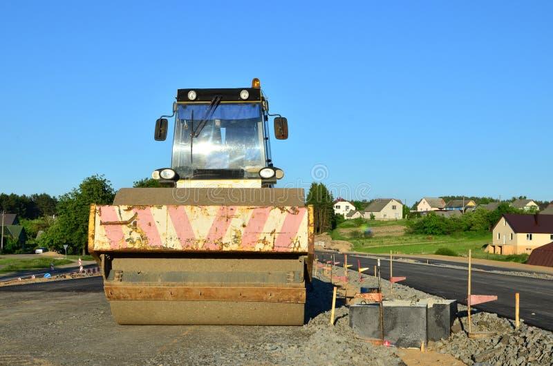 Asfaltera byggnationer med kommersiell reparationsutrustning V?grullar som j?mnar ny asfalttrottoar royaltyfri fotografi