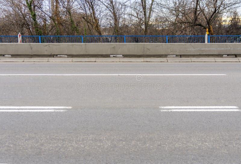 Asfaltera den tomma stadsvägen med trottoaren och gränd två för trafik arkivbilder