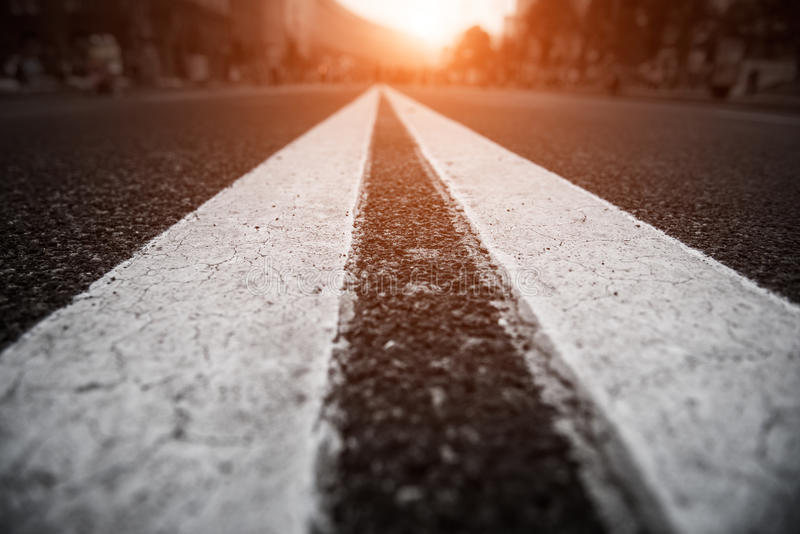 Asfaltera stadsvägen med vita linjer framåt och solnedgången royaltyfri fotografi
