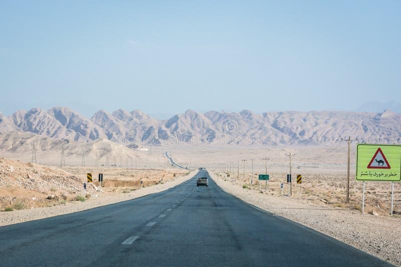 Asfaltera vägen i öken i Iran med tecknet med kamlet på vägen arkivfoto