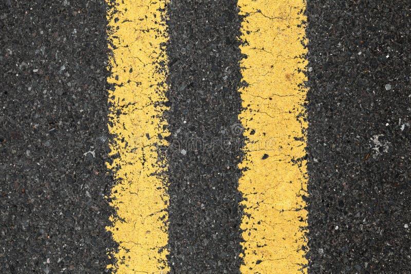 Asfaltera vägen med den gula dubbla delande linjen royaltyfri fotografi