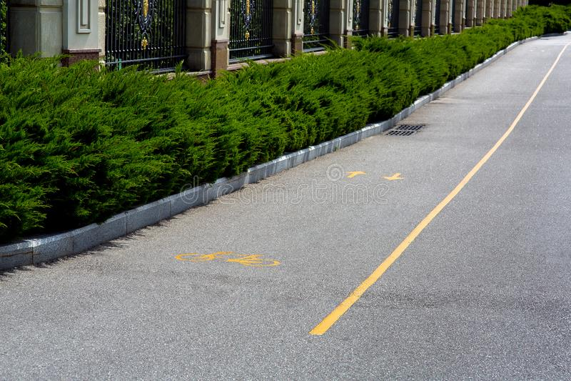 Asfaltera vägen med gul teckning för cyklar royaltyfri bild