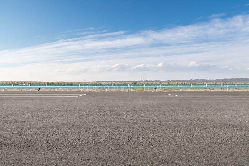 Asfaltera vägyttersida med blå himmel arkivfoto