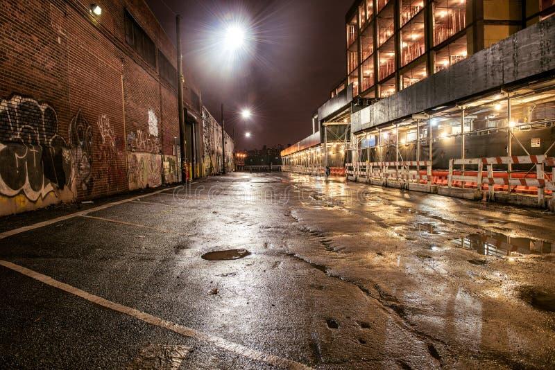 Asfalti la strada della via nella città di notte dopo la pioggia Parcheggio con i graffiti sui mura di mattoni immagini stock