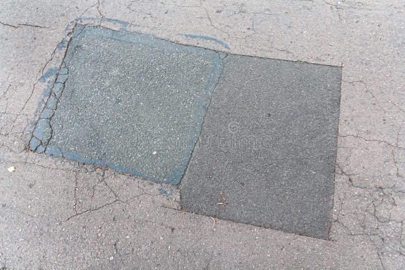 Asfalti la toppa del catrame sulla strada a terra concreta della pavimentazione della riparazione fotografie stock