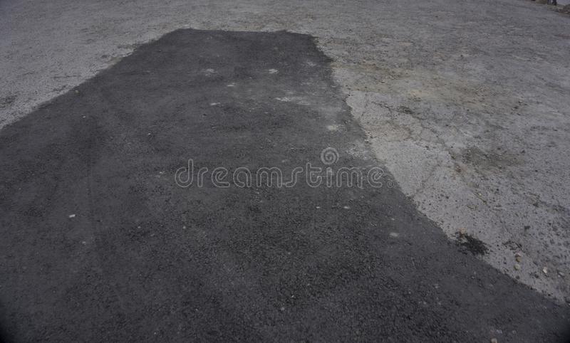 Asfalti la toppa del catrame sulla strada a terra concreta della pavimentazione della riparazione nel parcheggio immagine stock libera da diritti