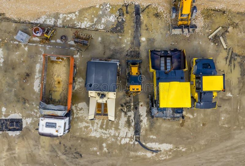 Asfalti le macchine ed il camion di diffusione ad un cantiere immagini stock