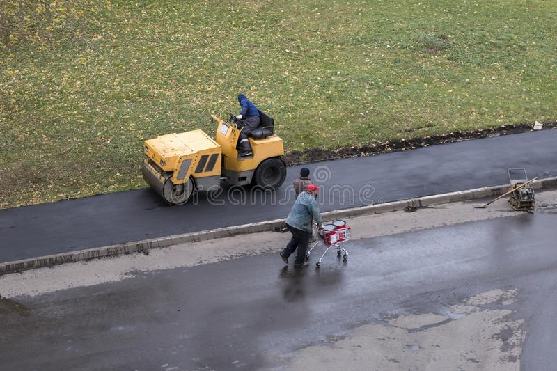 Asfalto fresco dos compactes do trabalhador de construção de estradas imagem de stock
