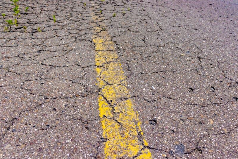 Asfalto rachado velho da estrada com linha contínua amarela, marcação do grunge na estrada coberto de vegetação abandonada imagem de stock royalty free