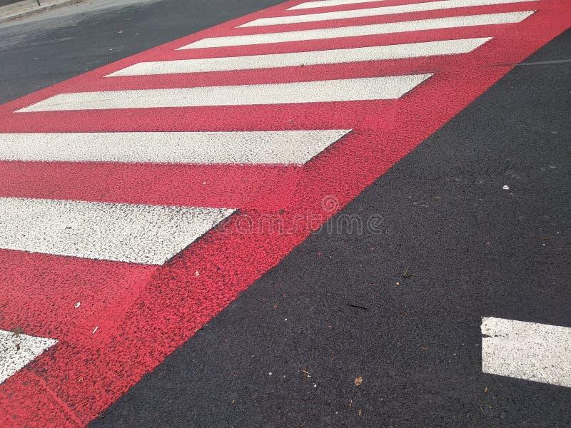 Asfalto vermelho em um cruzamento pedestre marcações da tira na estrada Seguran?a rodovi?ria regulamentos de tráfego, estrada do  foto de stock