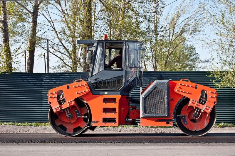 Asfaltowa brukowa maszyna Drogowy rolownik pracuje na nowym budowy drogi miejscu Boczny widok obraz stock