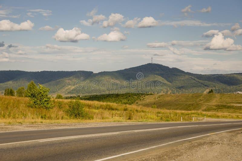 Asfaltowa droga i?? przez g?ry i ziele? lasy Drzewa i ich cienie na trawie Pogodny letni dzie? z niebieskim niebem ural zdjęcie royalty free