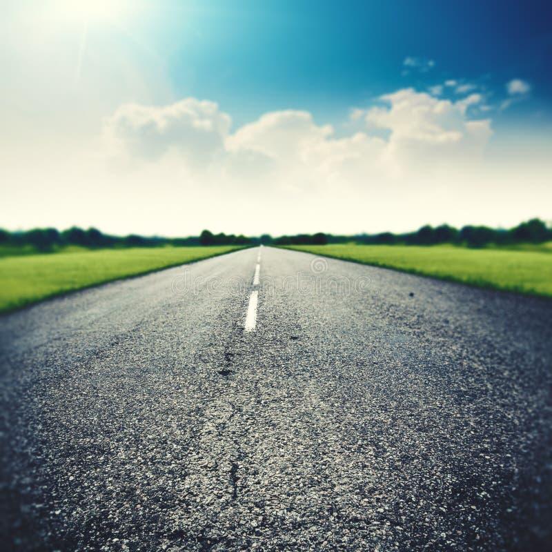 Asfaltowa droga pod szerokimi niebieskimi niebami zdjęcie stock