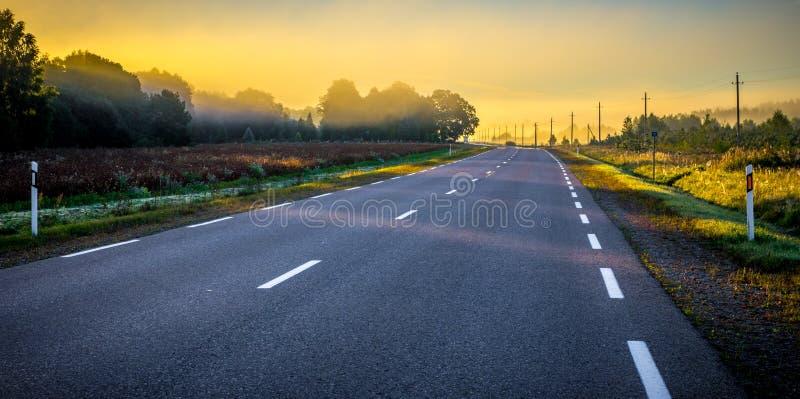 Asfaltowa droga przy wschodem słońca zdjęcie royalty free